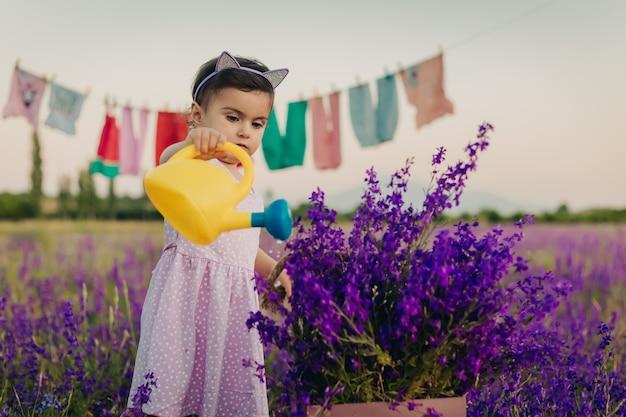 Portrait de petite fille debout dans un champ de lavande et arrosant des fleurs avec un arrosoir en plastique