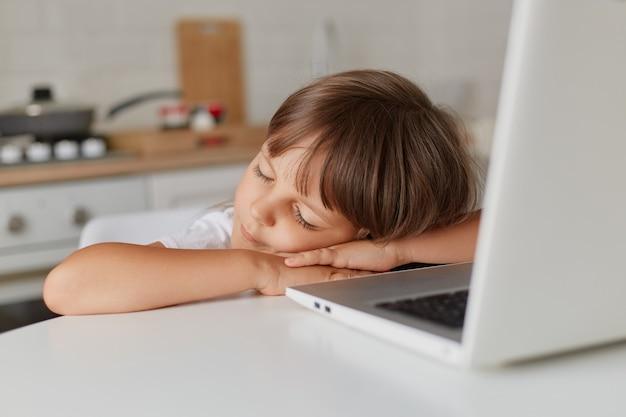 Portrait d'une petite fille dormant devant un ordinateur portable restant sur la table dans la cuisine, une petite fille d'âge préscolaire regarde un dessin animé et s'endort, enfance.