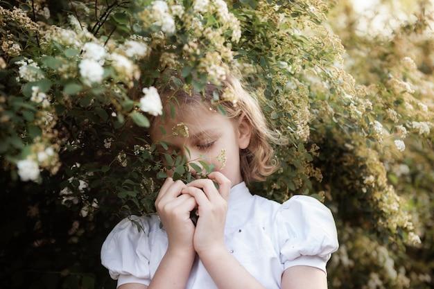 Portrait de petite fille douce aux longs cheveux blonds, gros plan, buisson en fleurs. concept de printemps.