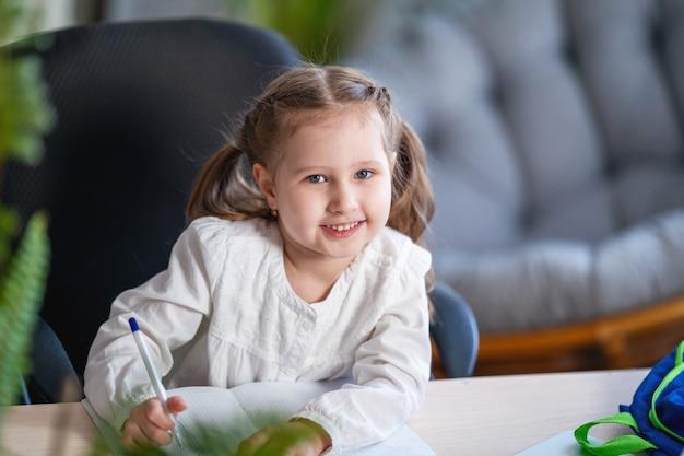Portrait d'une petite fille écrivant dans un cahier, étudiant à la maison.