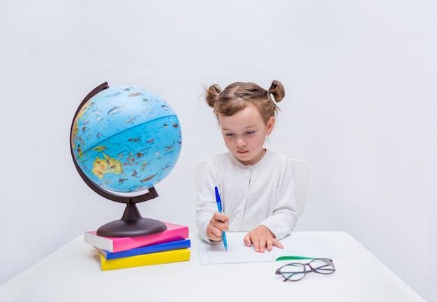 Portrait d'une petite fille élève écrit avec un stylo dans un cahier à une table sur un blanc isolé