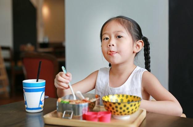 Portrait de petite fille enfant asiatique prenant son petit déjeuner le matin.