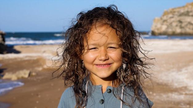 Portrait d'une petite fille enfant heureuse regardant la caméra et souriant à la plage.