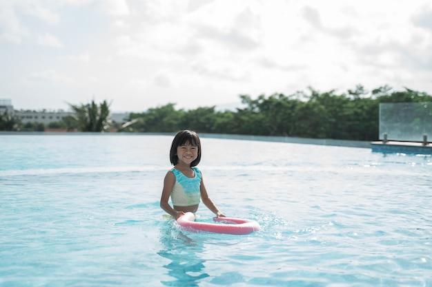 Portrait de petite fille essayant d'apprendre la natation dans la piscine seule