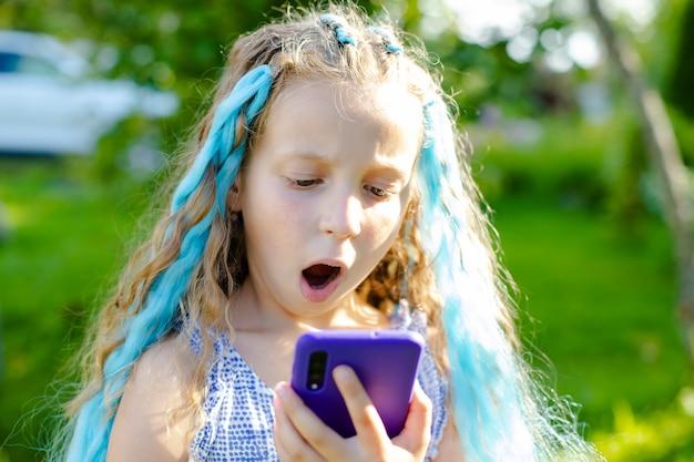 Portrait de petite fille excitée regardant l'écran du téléphone mobile