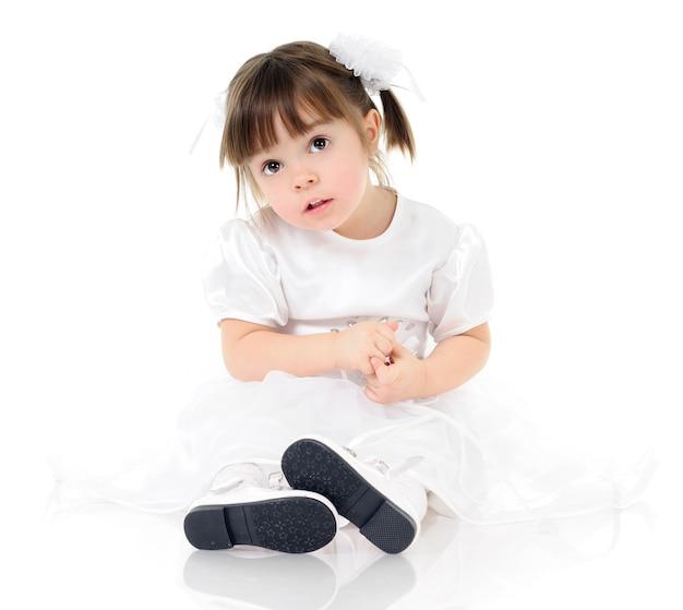 Portrait de petite fille avec une expression faciale drôle sur fond clair. enfant en vêtements blancs et accessoires pour cheveux