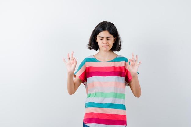 Portrait de petite fille faisant de la méditation avec les yeux fermés en t-shirt et à la vue de face détendue