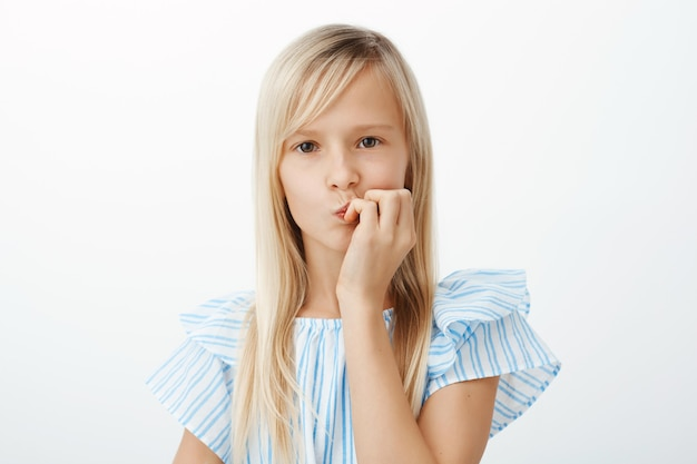 Portrait de petite fille focalisée concernée avec de longs cheveux blonds, plier les lèvres et se mordre les doigts, regarder, espacer pendant les grondements ou penser à des problèmes personnels sur un mur gris