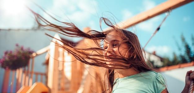 Portrait d'une petite fille heureuse assis sur une balançoire avec des cheveux longs volant