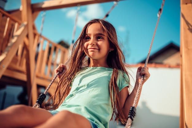 Portrait d'une petite fille heureuse assise sur une balançoire