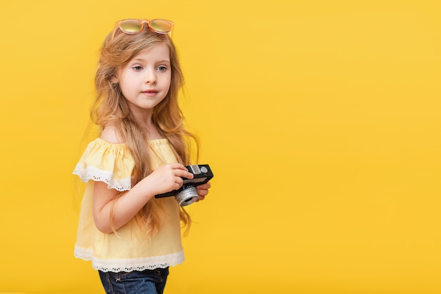 Portrait d'une petite fille heureuse aux cheveux longs avec un appareil photo rétro dans ses mains