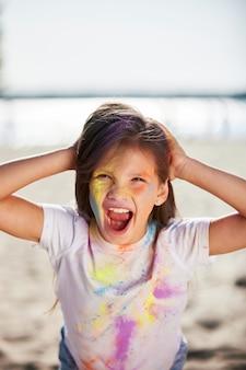 Portrait de petite fille heureuse d'enfant dans des peintures de houx