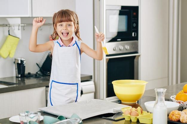 Portrait de petite fille heureuse excitée avec une brosse en silicone à la main appréciant la cuisson des biscuits à la maison