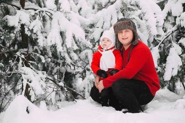 Portrait de petite fille heureuse en manteau rouge avec papa s'amuser avec la neige dans la forêt d'hiver,