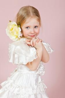 Portrait d'une petite fille heureuse avec une rose dans les cheveux rose