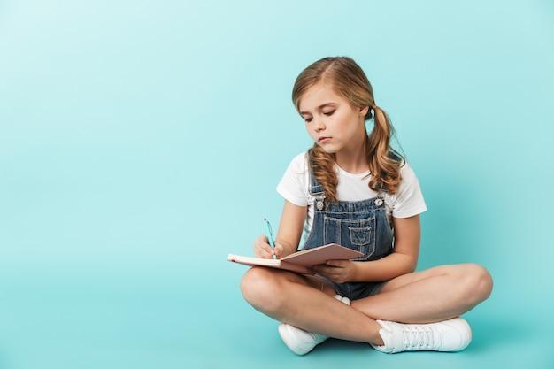 Portrait d'une petite fille isolée sur un mur bleu, écrivant dans un cahier