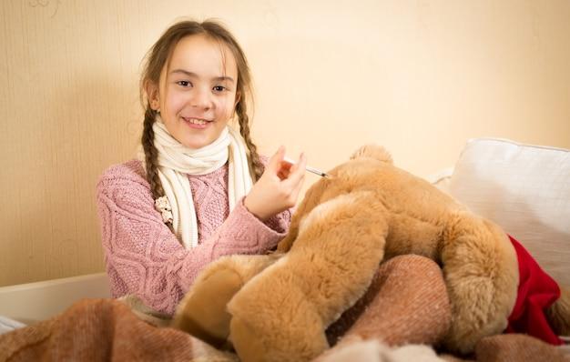 Portrait de petite fille jouant dans le docteur et faisant l'injection à l'ours en peluche