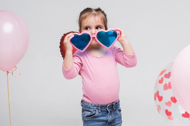 Portrait de petite fille jouant avec des lunettes