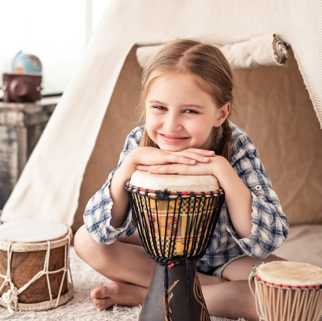 Portrait de petite fille jouant sur des tambours djembé africains traditionnels assis en wigwam dans la chambre des enfants