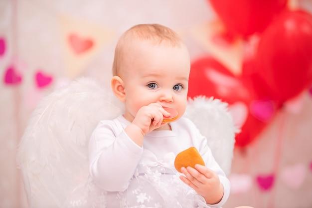 Portrait d'une petite fille joyeuse avec des ailes de plumes blanches, manger des cookies en forme de coeur