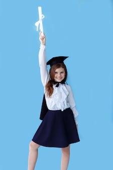 Portrait d'une petite fille joyeuse en chapeau de graduation souriant