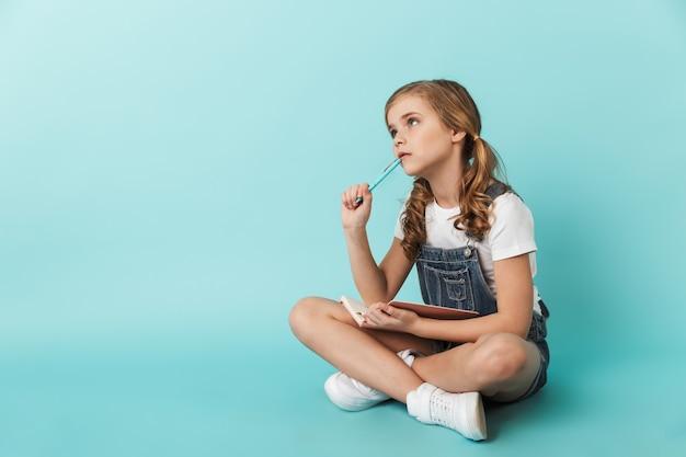 Portrait d'une petite fille joyeuse isolée sur un mur bleu, écrivant dans un cahier