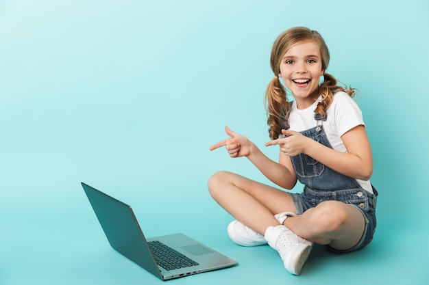 Portrait d'une petite fille joyeuse isolée sur un mur bleu, étudiant avec un ordinateur portable, pointant du doigt