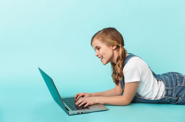 Portrait d'une petite fille joyeuse isolée sur un mur bleu, étudiant avec un ordinateur portable
