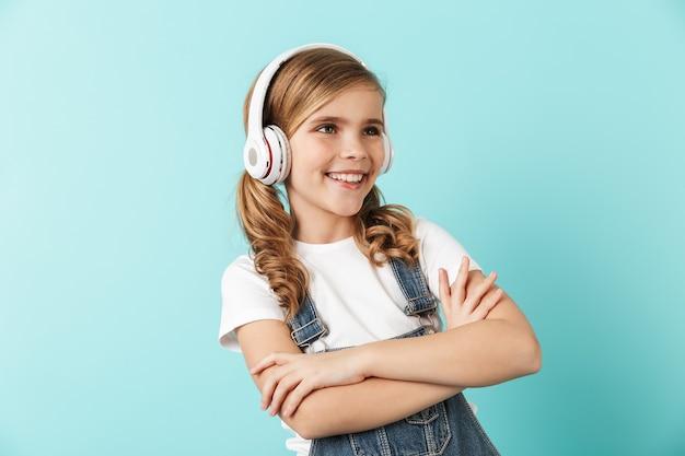Portrait d'une petite fille joyeuse isolée sur un mur bleu, portant des écouteurs