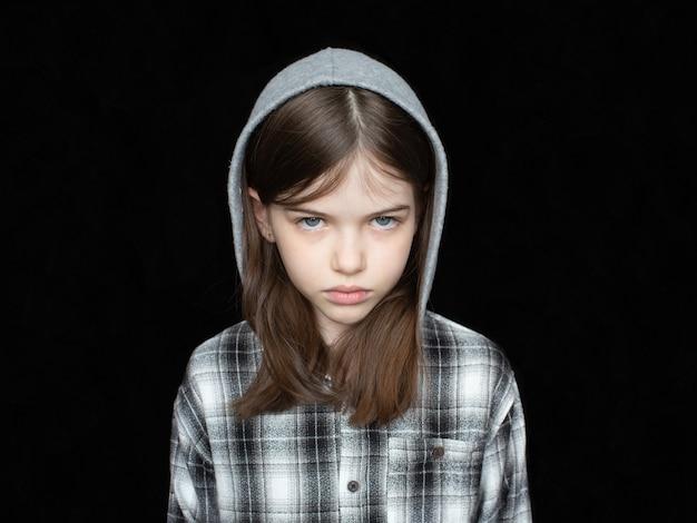 Portrait d'une petite fille en larmes offensée dans un sweat à capuche sur fond noir
