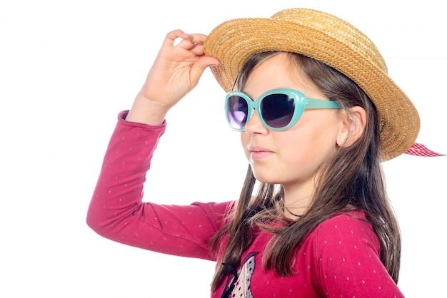 Portrait d'une petite fille avec des lunettes de soleil et un chapeau