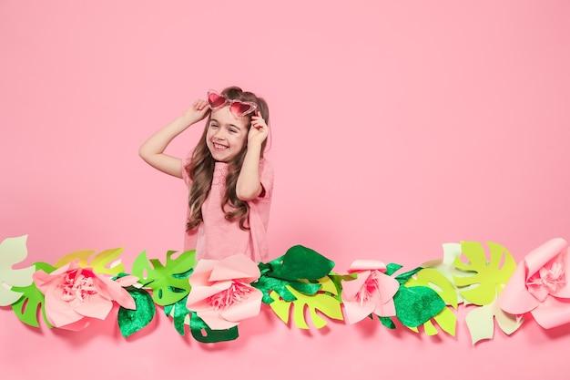 Portrait d'une petite fille avec des lunettes de soleil sur un mur rose