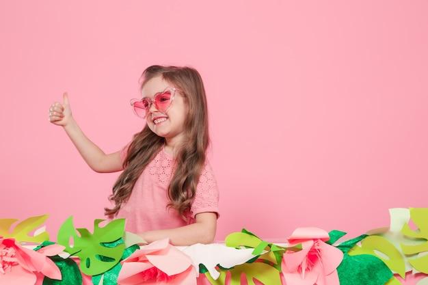 Portrait d'une petite fille avec des lunettes de soleil sur rose