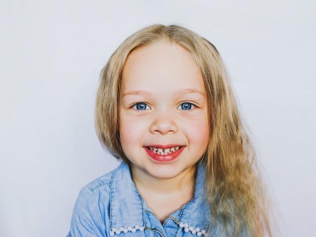 Portrait d'une petite fille magnifique aux yeux bleus, sur fond blanc