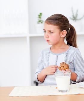 Portrait d'une petite fille mangeant des cookies