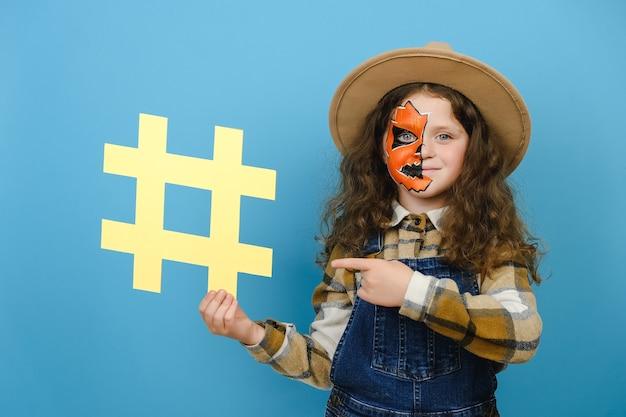 Portrait d'une petite fille avec un masque de maquillage d'halloween montre un symbole de hashtag, un regard positif sur la caméra, marquant un blog célèbre, un contenu viral, porte un chapeau, isolé sur fond de studio bleu