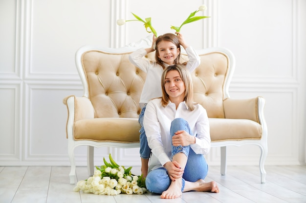 Portrait de petite fille et mère aimante avec des tulipes