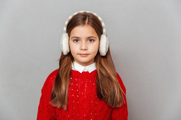 Portrait de petite fille mignonne dans le chandail et les cache-oreilles rouges