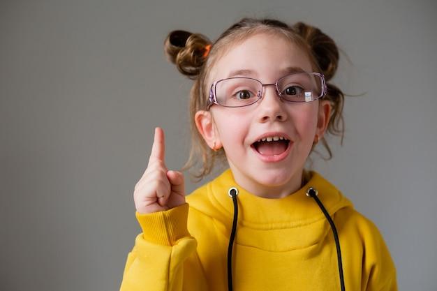 Portrait d'une petite fille mignonne et drôle dans des lunettes à monture noire dans un sweat à capuche jaune avec une coiffure amusante