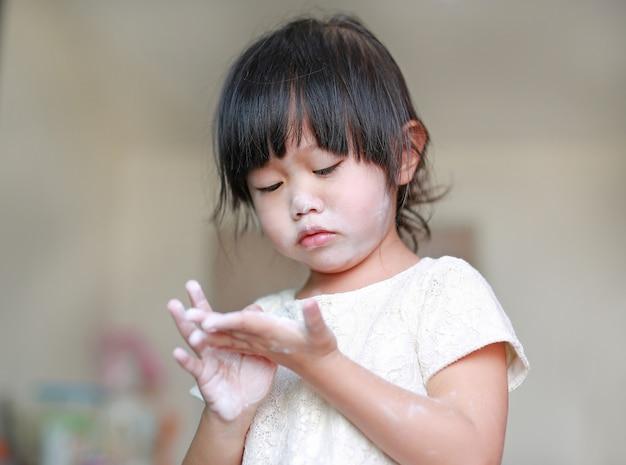 Portrait de petite fille mignonne avec de la poudre pour bébé
