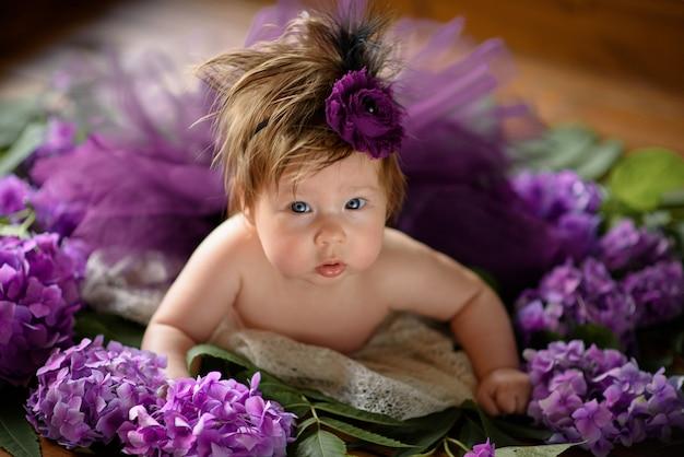 Portrait d'une petite fille mignonne (six mois). bébé se trouve aux couleurs de l'hortensia violet