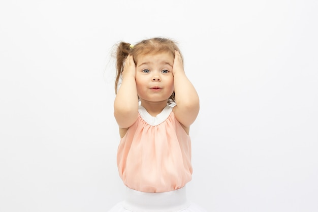 Portrait d'une petite fille mignonne surprise à lunettes de soleil sur fond rose. le modèle enfant s'amuse et fait de la publicité pour les produits pour enfants