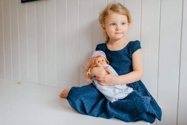 Portrait de petite fille mignonne tient sa belle barbie, se trouve dans la chambre de bébé lumineuse, regarde de côté