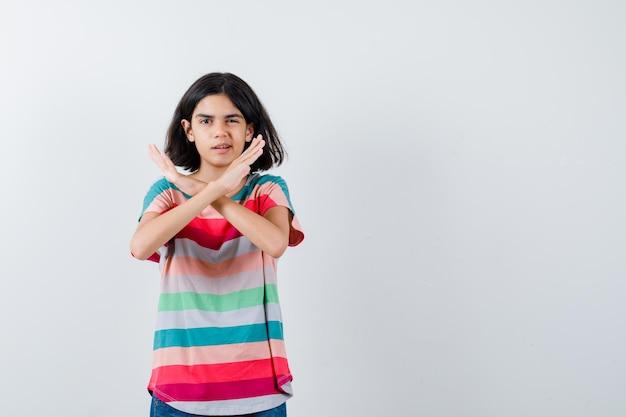 Portrait de petite fille montrant un geste de refus en t-shirt et à la vue de face confiante