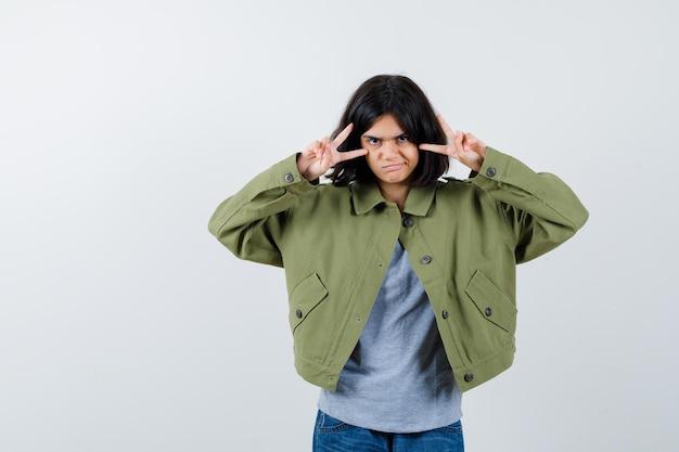 Portrait de petite fille montrant le signe de la victoire en manteau, t-shirt, jeans et vue de face chanceuse