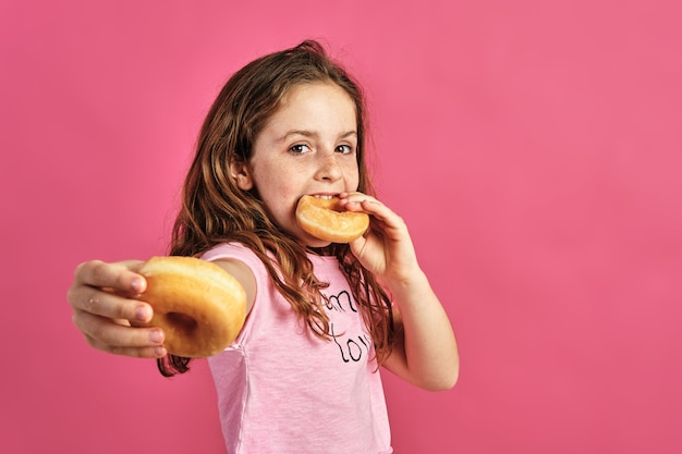 Portrait d'une petite fille offrant un beignet sur un mur rose
