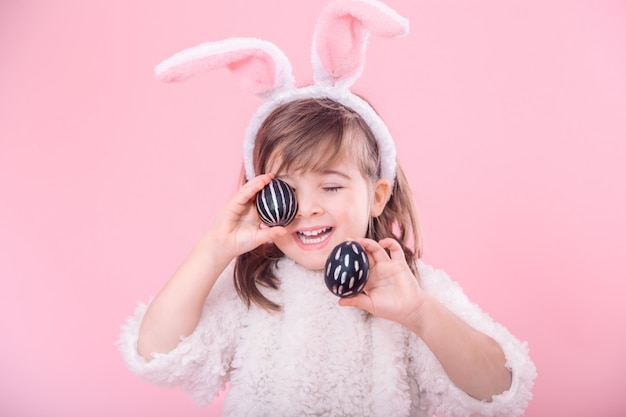 Portrait d'une petite fille avec des oreilles de lapin et des oeufs de pâques