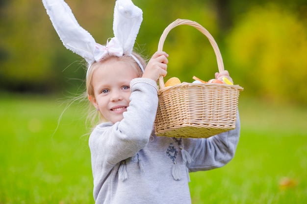 Portrait de petite fille avec un panier rempli d'oeufs de pâques printemps jour en plein air