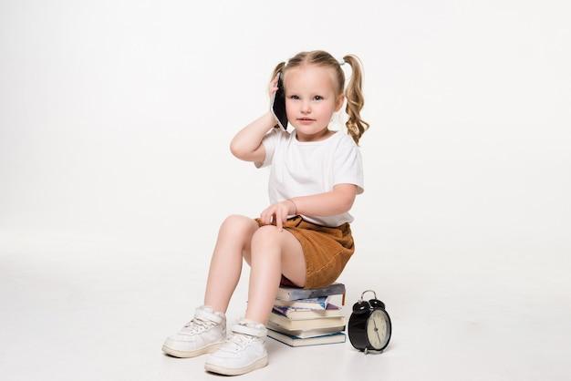 Portrait d'une petite fille parler téléphone assis sur une pile de livres.
