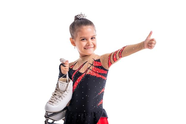 Portrait d'une petite fille patineuse artistique avec des patins dans ses mains montrant un geste de réussite